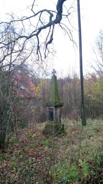 Kleines Denkmal vor der Hergisdorfer Kirche.